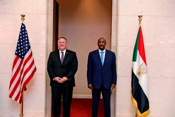 U.S. Secretary of State Mike Pompeo stands with Sudanese Gen. Abdel-Fattah Burhan, the head of the military side of the ruling sovereign council, in Khartoum, Sudan. Aug. 25, 2020
