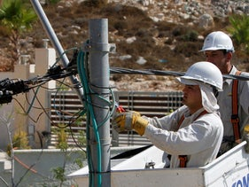 Electricians install new power transmission lines at a construction site in the West Bank city of Ramallah, September 3, 2012.