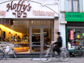 A Jewish boy rides his bike past a take-away restaurant in Antwerp, Belgium, January 16, 2015.