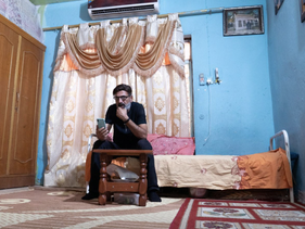 Mohammed al-Dahamat, brother of late civil society activist, Amjad al-Dahamat, speaks on the phone to Hasanain Alminshid, who fled Amarah after receiving threats for participating in anti-government protests, in Amarah, Iraq, October 12, 2020.