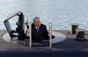 Prime Minister Benjamin Netanyahu climbs out after a visit inside the Rahav submarine after it arrived in the port of Haifa, January 12, 2016.