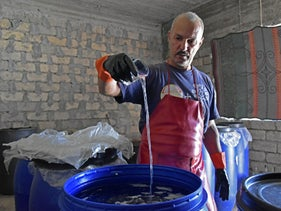 Saad Hussein pours liquid into a fermentation vat, a step in the process of producing arak from dates, October 14, 2020.