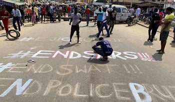 A demonstrator paints 'End Sars', referring to the Special Anti-Robbery Squad police unit, on a street during a protest demanding police reform in Lagos, Nigeria October 20, 2020. REUTERS/Seun Sanni