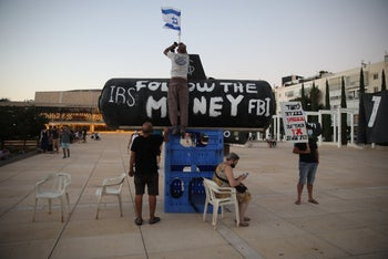 Protesters install a replica of a submarine with the slogan 'Follow the money' inscribed, Habima Sq., Tel Aviv, August 17, 2020.