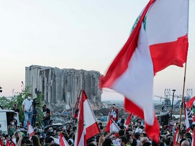 Lebanese protesters rally to mark the one year anniversary of the beginning of a nationwide anti-government protest movement, in front of the devastated port of the capital Beirut, October 17, 2020.