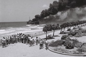 Israelis watch as the Etzel's ship Altalena burns after being shelled by the Palmach, off the coast of Tel Aviv, June 1948.