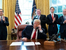President Donald Trump on a phone call with the leaders of Sudan and Israel with senior U.S. officials behind him at the White House, October 23, 2020, in Washington.