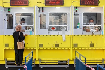 A woman is tested by a healthcare worker for the coronavirus at a mobile testing station, in East Jerusalem, July 21, 2020.