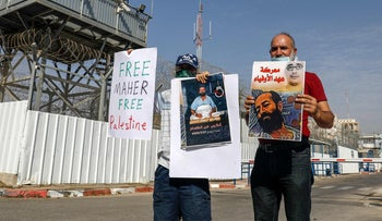 Activists lift placards during a demonstration calling for the release of Palestinian administrative detainees, including Maher Akhras, outside Ayalon prison in central Israel, October 24, 2020.
