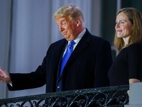 Donald Trump poses with Justice Amy Coney Barrett on a White House balcony after she was sworn in to serve as an associate justice of the Supreme Court, October 26, 2020.