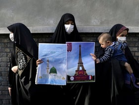 A protester holding banner of France's Eiffel Tower and Al Masjid Nabawi of Saudi Arabia, takes part in a protest to condemn the French magazine Charlie Hebdo, Tehran, Iran September 9, 2020.