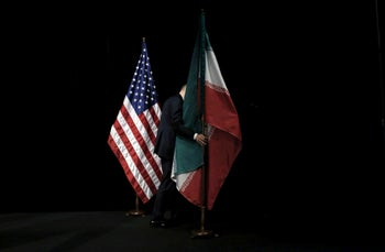 A staff member removing the Iranian flag from the stage during the Iran nuclear talks in Vienna, July 14, 2015.