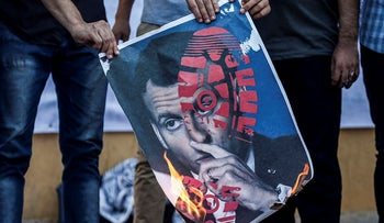 Supporters of Palestinian Islamist movement Hamas set fire to a portrait depicting French President Emmanuel Macron with a graphical shoe-print over it during a rally to protest his comments over Prophet Mohammed cartoons, outside the French Cultural Center headquarters in Gaza city on October 27, 2020