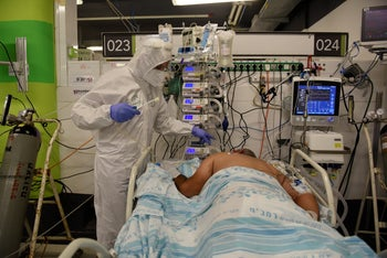A medical worker at Haifa's Rambam Health Care Campus provides care to a coronavirus patient, October 5, 2020.