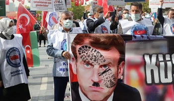 Protesters carrying a sign depicting Macron, in Ankara, October 27, 2020.