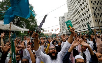 A man waves a dagger at a protest against the satirical French newspaper Charlie Hebdo, which reprinted a cartoon of the Prophet Mohammad. Karachi, Pakistan, September 4, 2020