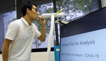 A staff member demonstrates the usage of Breathonix breathalyzer test kit developed by Breathonix, a start-up by the National University of Singapore, able to detect the coronavirus disease (COVID-19) within a minute according to the company, at their laboratory in Singapore October 29, 2020