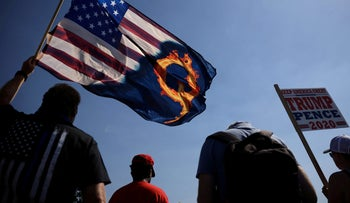 A Trump supporter holds an U.S. flag with a QAnon reference in Oregon city, Oregon, September 7, 2020.