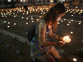 An Israeli woman lights a candle to the memory of Yitzhak Rabin, as anti-government protests coincide with the 25th anniversary of the former prime minister's assassination, Tel Aviv, October 29, 2020.