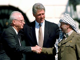 Bill Clinton (C) looks on as Yitzhak Rabin (L) and Yasser Arafat shake hands at the White House, September 13, 1993.