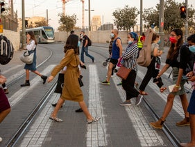People wear masks while walking in the streets in Jerusalem, October 29, 2020.