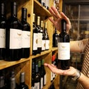 A shop owner holds a bottle of wine from the Golan Heights Winery as he poses for a photograph at his store in Jerusalem October 28, 2020.
