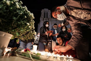 People light candles outside the Notre-Dame de l'Assomption Basilica in Nice on October 29, 2020.