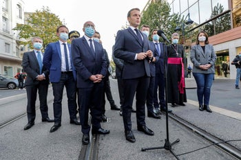 French President Emmanuel Macron (C) speaks to the press outside the the Notre-Dame de l'Assomption Basilica in Nice on October 29, 2020.