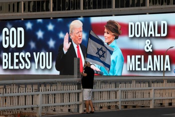 A man waves the Israeli flag during a protest against Benjamin Netanyahu, backdropped by a billboard supporting President Donald Trump and first lady Melania Trump,  in Tel Aviv, October 3, 2020.