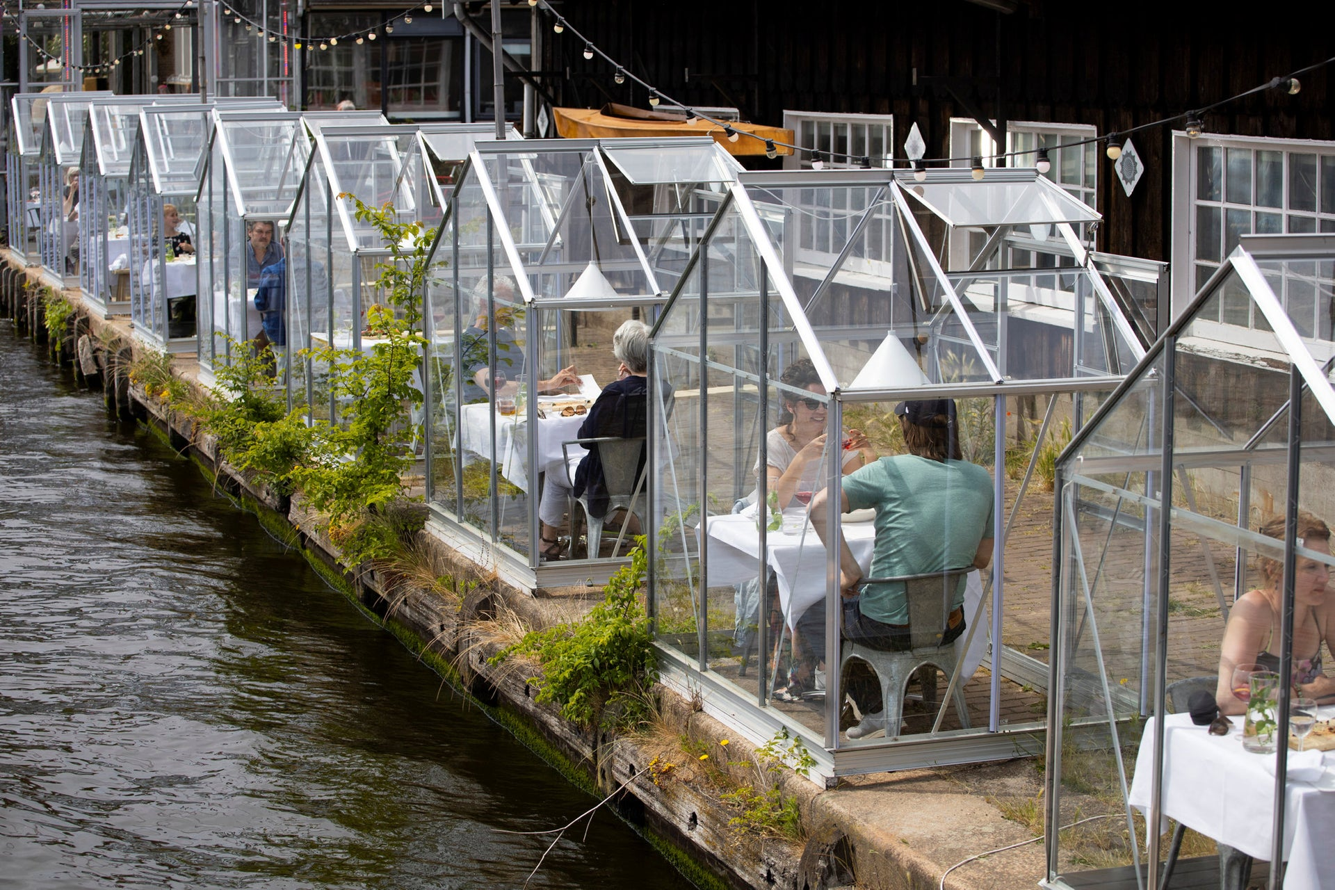 Customers seated in small glasshouses enjoy lunch at the Mediamatic restaurant in Amsterdam, Netherlands, June 1, 2020.