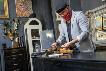 A barber, who will be allowed to operate by appointment after the easing of coronavirus regulations, preparing his tools, October 29, 2020.