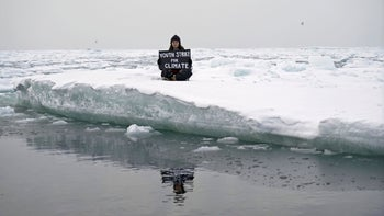 "Environmental activist and campaigner Mya-Rose Craig, 18, holding a cardboard sign reading ""youth strike for climate"" as she sits on the ice floe in the middle of the Arctic Ocean, September 20, 2020."