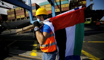 A worker carries Israeli and Emirati flags, after containers carrying goods from the UAE were unloaded at Haifa's port, October 12, 2020.
