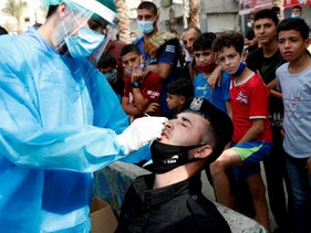 A Palestinian health worker collects a nasal swab sample from a police officer after Friday prayers in the Jabaliya refugee camp, in the Gaza Strip, Oct. 30, 2020