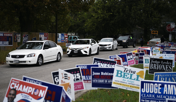 A line of cars drive in for an event encouraging community members to vote in the upcoming presidential election at an early voting site in Houston, Texas, October 25, 2020.