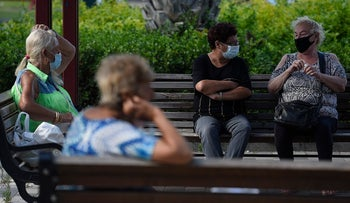 Older women seated outdoors during the coronavirus pandemic in Haifa. For illustration purposes only.