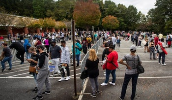 Hundreds of people wait in line for early voting in Marietta, Georgia, October 12, 2020.