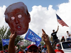 A man holds up a cardboard cutout of President Donald Trump in Miami, November 2020.