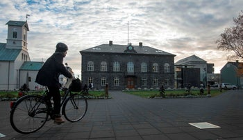 A woman cycles past the Althingi Parliament building in Reykjavik, Iceland, October 24, 2017.