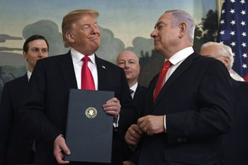 President Donald Trump smiling at Prime Minister Benjamin Netanyahu after signing a proclamation in the Diplomatic Reception Room at the White House in Washington, March 25, 2019.
