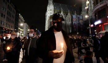 People hold candles outside St. Stephen's cathedral, following a religious mass for the victims of a gun attack in Vienna, Austria, November 3, 2020.