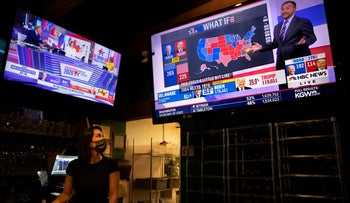 A bartender watches election results on television at a bar and grill in Portland, Oregon, November 3, 2020.