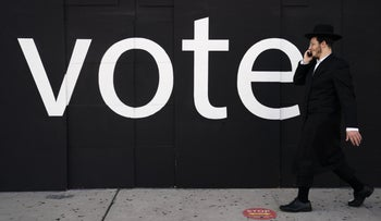 """A Jewish man walking past a boarded-up store in Los Angeles with the word """"Vote"""" on it, November 2, 2020."""