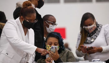 People look at cell phones as votes continue to be counted in Detroit, Michigan, November 4, 2020.