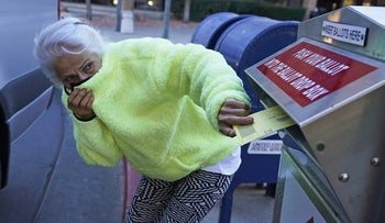 A woman inserts her ballot into a drops box in Salt Lake City, November 2, 2020.