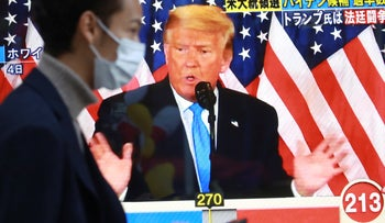 A man walks past at a TV screen showing U.S. President Donald Trump during a news program reporting U.S. presidential election in Tokyo, Japan, November 5, 2020.