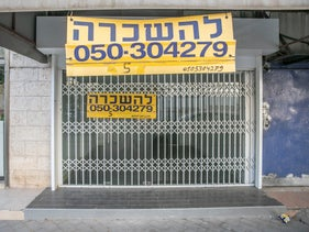 """A """"for rent"""" sign on a store in Holon, November 2020."""