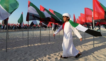 An Emirati boy walks among UAE national flags set up to celebrate the country's Flag Day in Dubai, November 3, 2020.