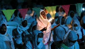Ethiopian Orthodox Christians light candles and pray for peace during a church service at the Medhane Alem Cathedral in Addis Ababa, Ethiopia, November 5, 2020.