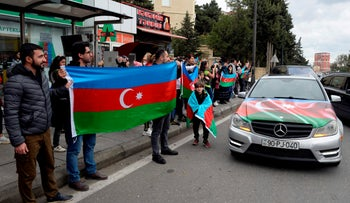 A man holds Azeri flag as he celebrates the capture the town of Shusha in Baku on November 8, 2020, during the ongoing military conflict between Armenia and Azerbaijan over the breakaway region of Nagorno-Karabakh.